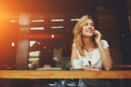 Collaboration with common loyalty currencies - woman on the phone in a cafe