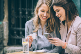 How sharing can improve the value of loyalty programs - two woman looking at their phones