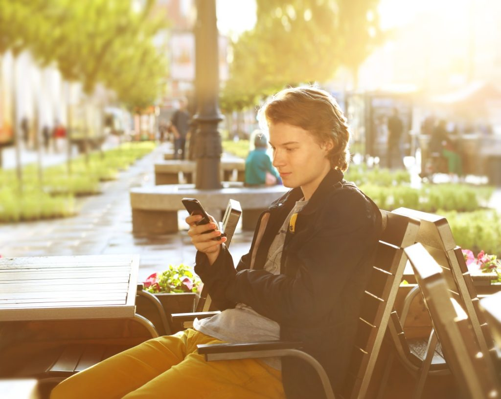 Top 5 ways to make loyalty programs more effective - teenager outside a cafe on his phone
