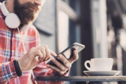 Top loyalty trends for 2018 and what they mean for brands and customers - a man with headphones and his phone having a coffee